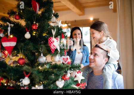 Young family with daugter at Christmas tree at home. - Stock Photo