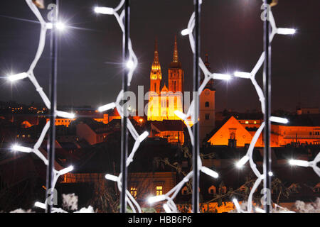 Zagreb cathedral seen through an illuminated fence in Christmas time - Stock Photo