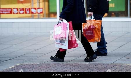 Black Friday and Christmas shopping in Brighton UK with shoppers carrying plastic and paper bags - Stock Photo