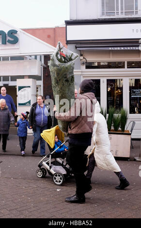 Man with his family carrying a newly bought real Christmas tree in Sutton Surrey UK December 2016 - Stock Photo