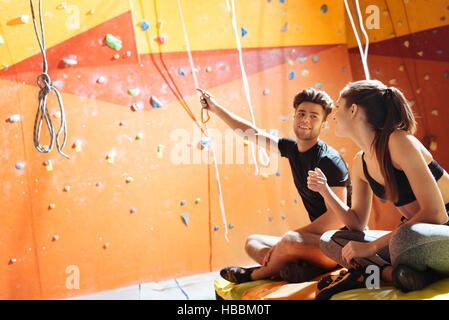 Young couple giving high five in a climbing gym - Stock Photo