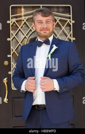 Unshaven groom in a blue suit - Stock Photo