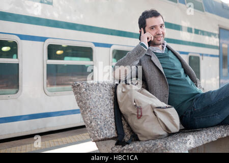 Man talking on the phone in a train station platform - Stock Photo