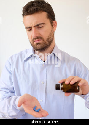 Portrait of a man taking a pill - Stock Photo