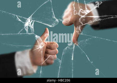 Thumbs Down and Up behind a broken Window - Stock Photo