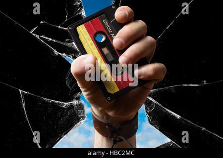 Hand holding east german Musicassette through broken Glass - Stock Photo