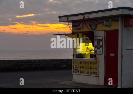 West Bay, Dorset, UK.  5th December 2016.  UK Weather.  a cloudy and misty sunset behind an ice-cream kiosk on the - Stock Photo