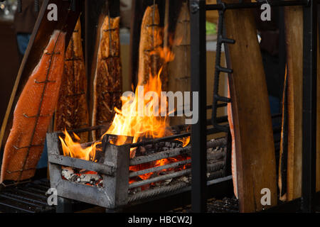 A photograph of some salmon being cooked over open flames at the Christmas markets in Basel, Switzerland. - Stock Photo