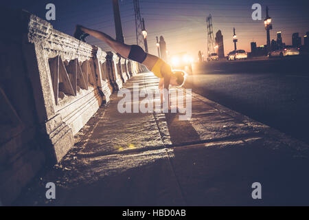 Young woman doing handstand on bridge - Stock Photo