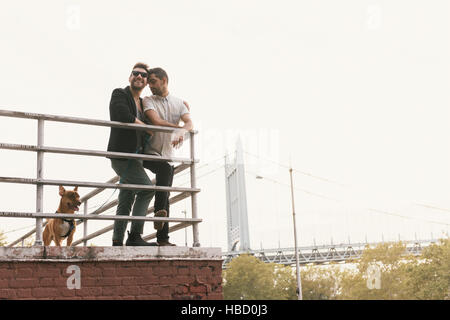Affectionate young male couple on riverside with dog, Astoria, New York, USA - Stock Photo