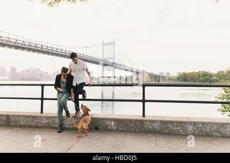 Young male couple on riverside looking at dog, Astoria, New York, USA - Stock Photo