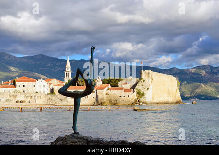 Sunset view of old town Budva: Dancing girl against ancient walls and red tiled roof. Montenegro, Europe. - Stock Photo