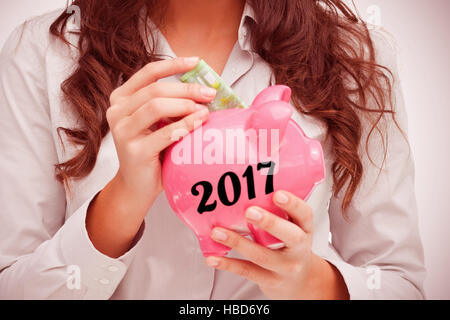 Composite image of brunette putting money in a piggy bank - Stock Photo