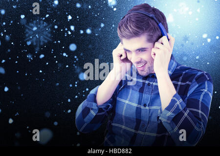 Composite image of hipster smiling while wearing headphones - Stock Photo