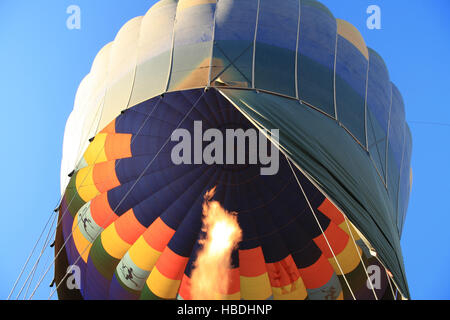 Flame warming a hot air balloon as it rises into a clear blue sky - Stock Photo