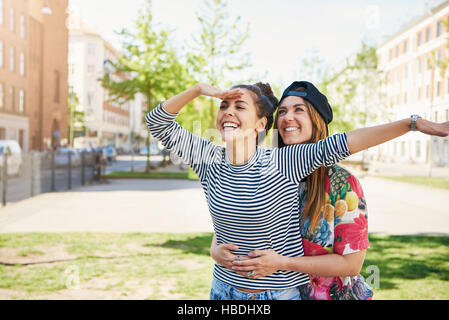 Pair of joyful loving sisters embracing and looking to outward and to the side with gesture as if to find something - Stock Photo