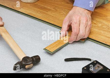 Master works on laying laminate panels - Stock Photo
