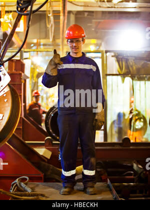 Workers fitters and welders in protective clothing and a helmet. Working in the operating industrial facilities. - Stock Photo