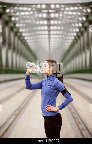 Young runner resting, drinking water on green steel bridge - Stock Photo