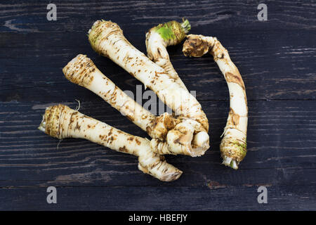 Fresh horseradish roots on wooden background - Stock Photo