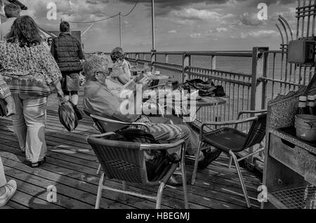 Southwold, England. Elderly people enjoying the sunny weather sitting along Southwold pier drinking tea and reading - Stock Photo