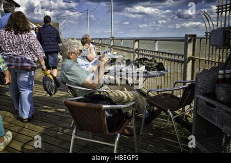 Southwold, England UK. Elderly people enjoying the sunny weather sitting along Southwold pier drinking tea and reading - Stock Photo