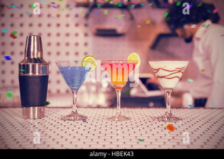 Composite image of various cocktails drinks and shaker on bar counter - Stock Photo