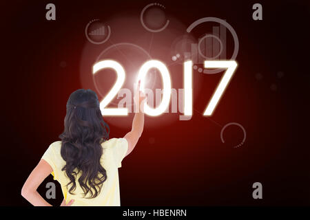 Composite image of brunette pointing in rear view - Stock Photo