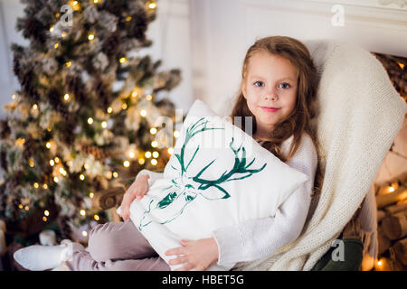girl at Christmas, xmas tree in the background, beautiful young kid wrapped in a blanket, she smiles - Stock Photo