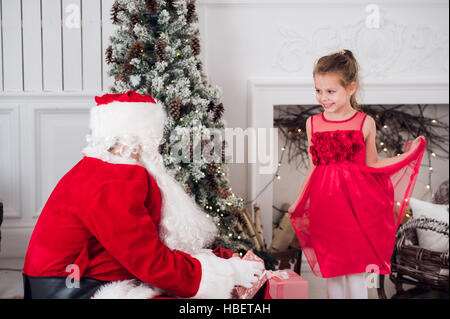 Santa Claus and children opening presents at fireplace. Kids father in costume wearing beard open Christmas gifts. - Stock Photo