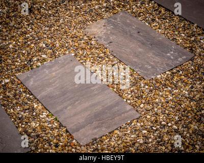 Paving set within gravel in garden path - Stock Photo