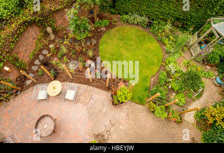 Modern garden seen from above with circular lawn and block paved patio - Stock Photo