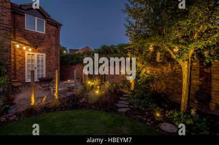 Modern garden design at dusk with contemporary wire shopping trolley chairs for seating and large Kadai firebowl - Stock Photo