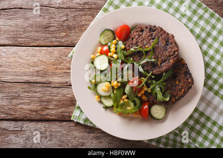 Black bean burger with a salad of fresh vegetables close-up on a plate. Horizontal view from above - Stock Photo