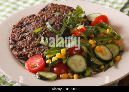 Vegetarian food: black bean burgers and a salad of fresh vegetables close-up on a plate. horizontal - Stock Photo