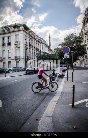 young woman visiting Paris with bicycle - Stock Photo