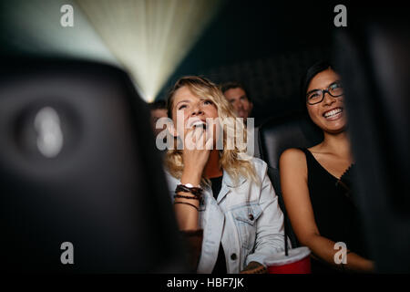 Smiling young women in cinema hall eating popcorn and watching movie - Stock Photo
