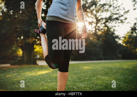 Cropped shot of fitness woman stretching legs. Female model exercising in the morning at city park.