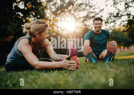 Fitness couple stretching outdoors in park. Young man and woman exercising together in morning. - Stock Photo