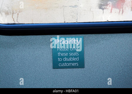 sign for priority seats on a bus for disabled customers in the uk - Stock Photo