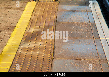 yellow lines and textured area of edge of train platform in the uk - Stock Photo