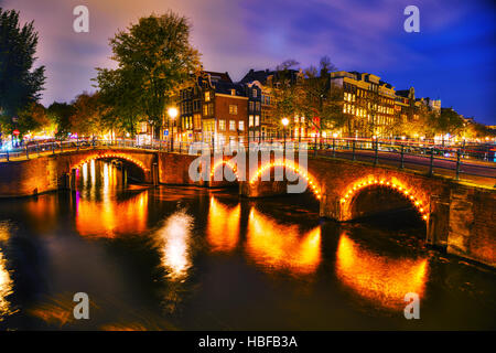 Amsterdam city view with canals and bridges at night - Stock Photo