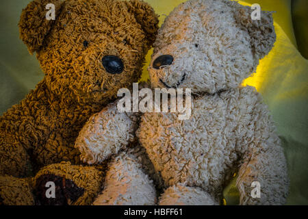 Two Teddy Bears sit embracing one another. One is smiling and the other is confused - Stock Photo