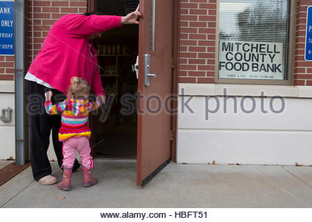 A woman arrives at the Mitchell County Food Bank in Osage, Iowa to receive donated food for her family. - Stock Photo
