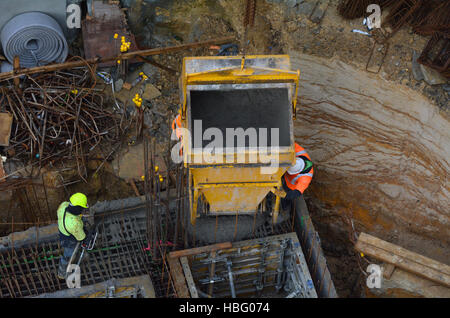 Aerial to view of concreting work: construction site worker during concrete pouring into form work at building area - Stock Photo