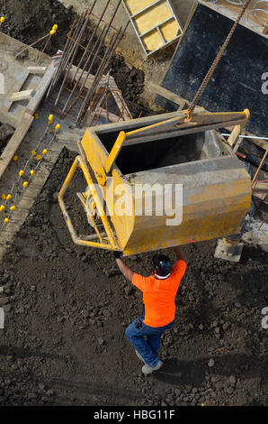 Aerial to view of concreting work: construction site worker during concrete pouring into formwork at building area - Stock Photo