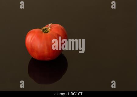 One big organic tomato on a black background - Stock Photo
