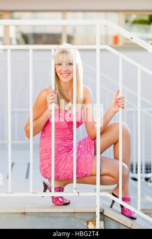 Happy young woman in bright Pink minidress behind White fence squat squatting sideways looking at camera smile smiling - Stock Photo
