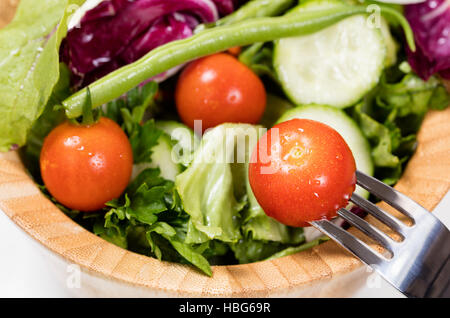 Salad with cherry tomatoes in wooden bowl - Stock Photo