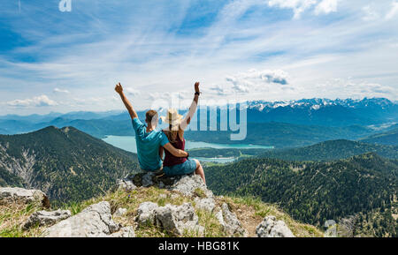 Young couple with arms in air, view of Lake Kochel from Heimgarten peak, left Herzogstand, Upper Bavaria, Bavaria, - Stock Photo